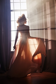 朝夕の太陽の窓の近くのセクシーな女性少女のシルエット。太陽の光でファッションブロンドの女性。日光は女性の体に当たります。窓に妖精の魔法の光