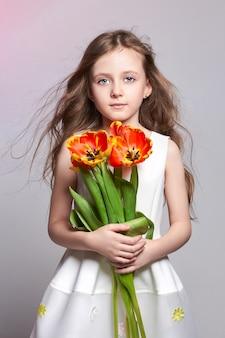 手にチューリップとファッションの赤い髪の少女。明るい色の背景のスタジオ写真。誕生日、休日、母の日、学校の初日