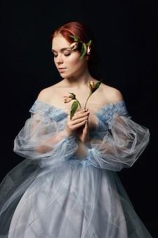 本の表紙に彼女の手の中世の花を持つ女性の肖像画。長い髪の少女の完璧な自然の美しさ