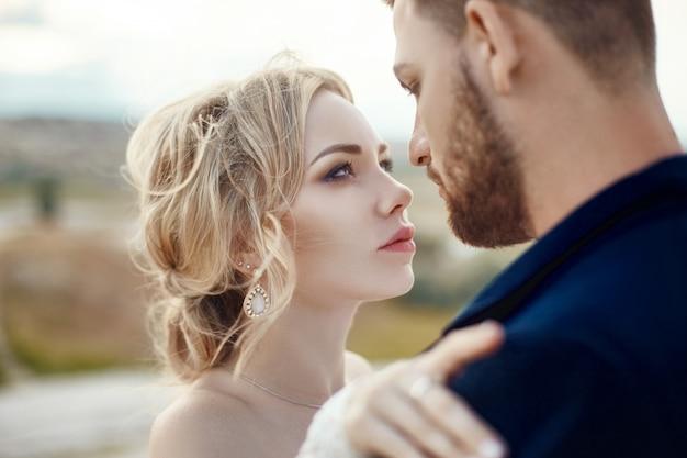 Пара в любви обнимает и целует в сказочных горах на природе. девушка в длинном белом платье с букетом цветов в руках, мужчина в пиджаке. свадьба на природе, отношения и любовь