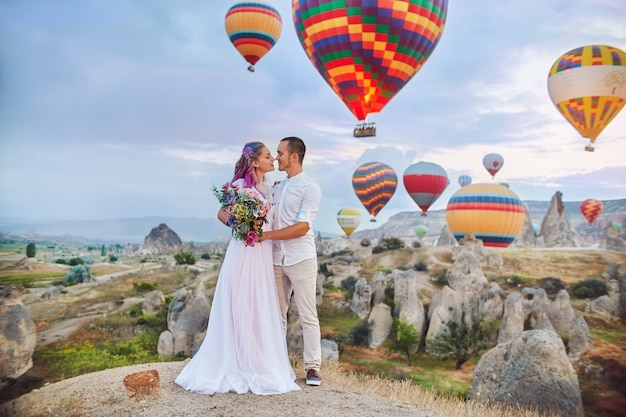 愛のカップルは、カッパドキアの風船の背景に立っています。丘の上の男女は、多数の空飛ぶ風船を見ています。トルコのカッパドキアのおとぎ話の山々の風景。自然の結婚式