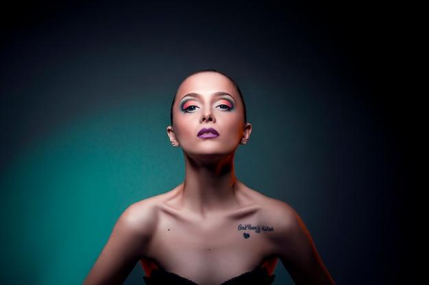 赤い髪の女性少女の顔に美容アートメイク。緑の背景に大きな青い目を持つ完璧な女の子。顔と体のスキンケアのためのプロの化粧品