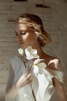 女の子の体に豪華な白いウェディングドレス。ウェディングドレスの新しいコレクション。朝の花嫁、結婚式前に新郎を待っている女性。ロングドレスの若い花嫁