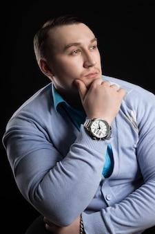 青いシャツと黒い背景にカーディガンで大きな筋肉を持つ実業家重量挙げの肖像画。パワーアスレチックでアスレチック男性フィットネスコーチ
