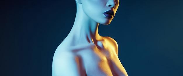 青と赤のシャドウトーンの女性の明るい対照的な美容化粧肖像画。完璧なきれいな肌と顔のメイク、ふっくらした唇に濃い口紅