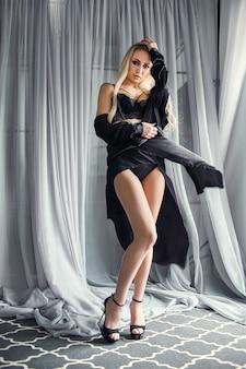 Сексуальная блондинка в черном нижнем белье идеальная фигура