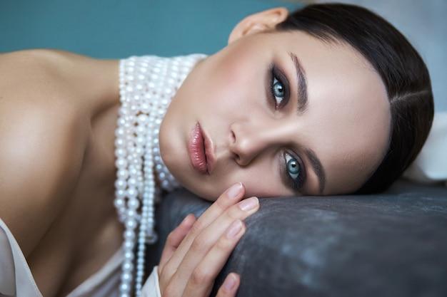 長く白いドレスを着たソファーに座っている美しい細いブルネットの少女。首にジュエリーを持つ女性の肖像画。女性の完璧な髪型と化粧品、軽いドレスの新しいコレクション