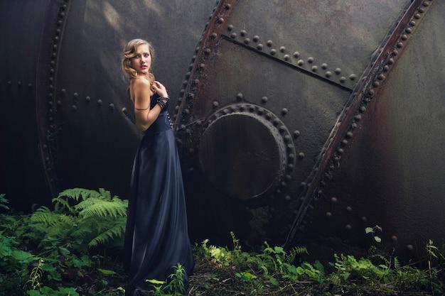 古い廃工場で黒のドレスでブロンドの女の子。スチームパンク