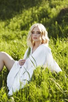 長い白いドレスの少女は、フィールドの草の上に座っています。光のドレスで太陽の下で金髪の女性。安静時と夢、彼女の顔に完璧な夏のメイクの女の子