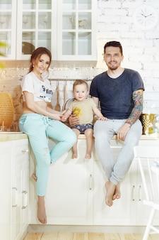 Супружеская пара и их маленький ребенок ребенок на руках. молодая семья дома с утра на выходной. радостные и счастливые лица обнимаются и веселятся