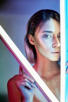 ランジェリーのネオンの光でセクシーな女性。ネオンと少女の顔のまぶしさ。明るいコントラストの光の壁にスパンコールで裸の女性。美しいメイクとブロンド