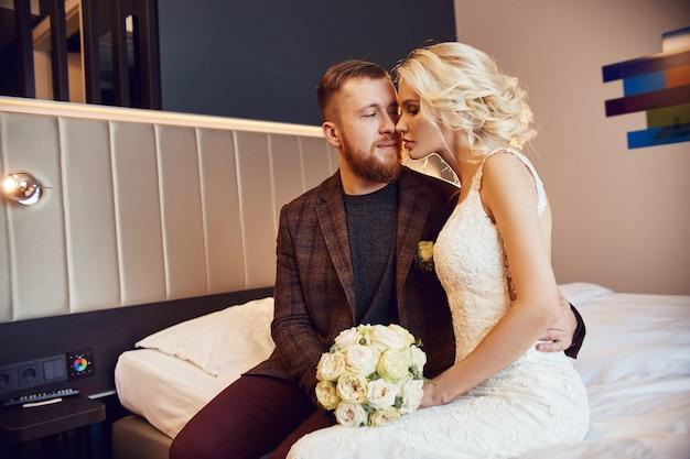 朝、ホテルの部屋で新婚夫婦は、結婚式を期待して抱き合ったり、お互いを見たりするベッドの上に座っています。長いひげを生やしたヒップスター新郎と金髪の花嫁のウェディングドレス