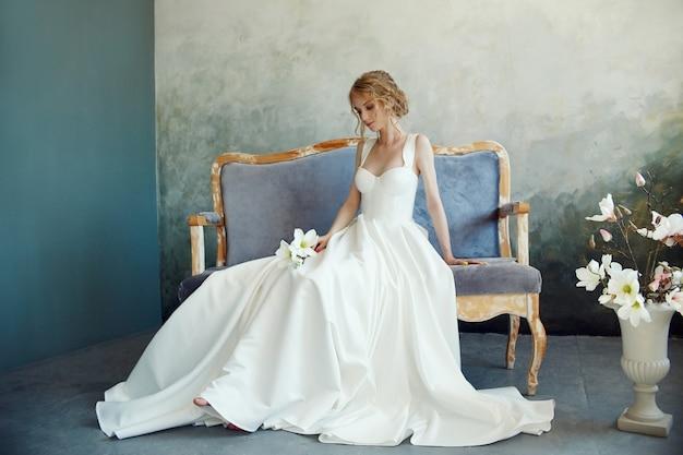 完璧な花嫁、長い白いドレスの少女の肖像画。美しい髪ときれいな繊細な肌。結婚式の髪型金髪の女性。彼女の手に白い花を持つ少女