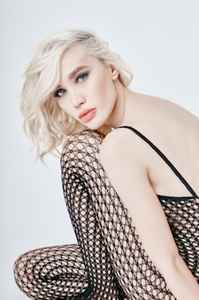 床に座って完璧なボディとランジェリーボディースーツで裸のセクシーなブロンドの女性。エロティックな女の子のネットにフェチランジェリー。完璧な姿の女性