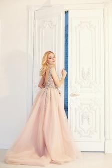 大きな白いドアの近くの美しい長いイブニングドレスの女性のファッションの肖像画。豪華なインテリア、完璧な姿と髪の少女