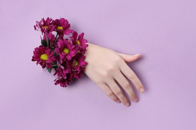 紫色の紙の穴に花を持つ美手