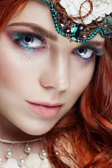 Рыжая девушка с ярким макияжем и большими ресницами.