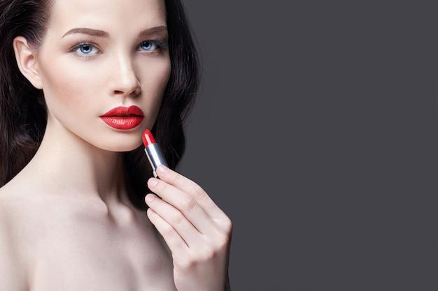 若いブルネットの女性は唇の赤い口紅を塗料します。