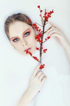 手に赤い果実を持つ木の枝女性ブロンドの濡れた髪明るく美しいアートメイク