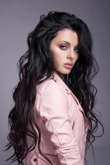 床に長い髪のピンクの革のジャケットで美しい女性。セクシーなブルネットの少女