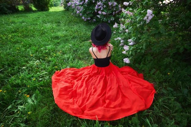 Фасонируйте девушку с призванием красных волос, портрет весны в сиреневых цветах в лете.