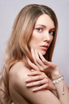 Портрет красоты женщины с длинными волосами, серьгами в ушах и дорогими украшениями на руках