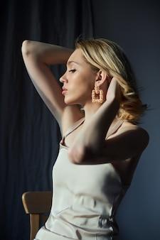 Блондинка с ювелирными серьгами в ушах сидит у окна в лучах вечернего солнца.