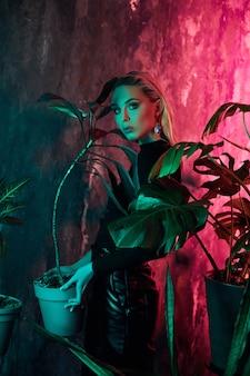 熱帯の葉とネオンの光とファッションの女性