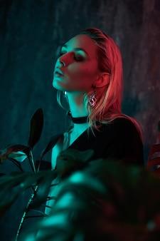 熱帯群葉ネオンの光の中でファッションの女性の肖像画。濡れた髪、完璧な姿とメイク