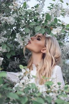 リンゴの木の枝に夏のブロンドの女性