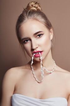 セクシーなファッションの若いブロンドの女の子の髪の宝石類の首