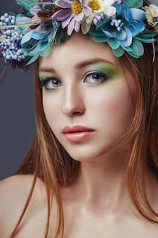 彼女の頭の上の青い花の花輪を持つ女性
