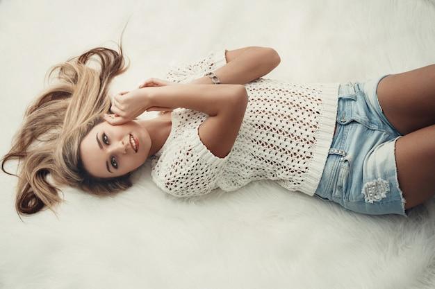 ベッドに横になっている美しい魅力的なブロンドの長い髪