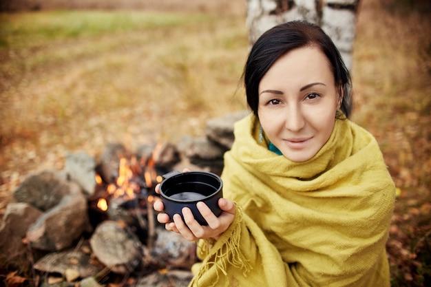 手で熱いお茶のマグカップを持つ女性の肖像画