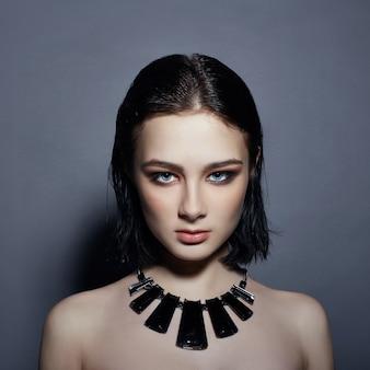 セクシーなファッションブルネットの少女は黒い髪の宝石を持っています