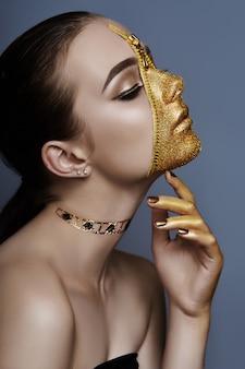 Креативная мрачная косметика для лица девушки золотистого цвета на молнии