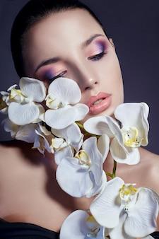 顔の近くの白い蘭の花を持つ女性