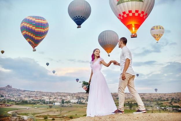 愛のカップルは風船の背景の上に立つ