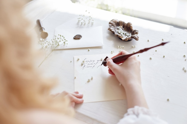 女の子は家に座っている彼女の最愛の人に手紙を書く