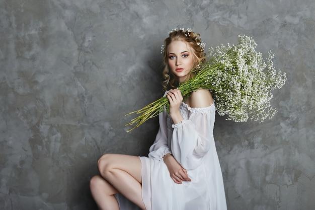 女の子の白い光のドレスと巻き毛