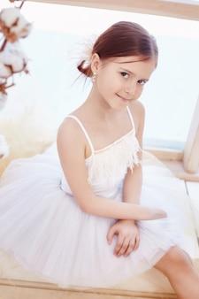 若いバレリーナの女の子はバレエの準備をしています。