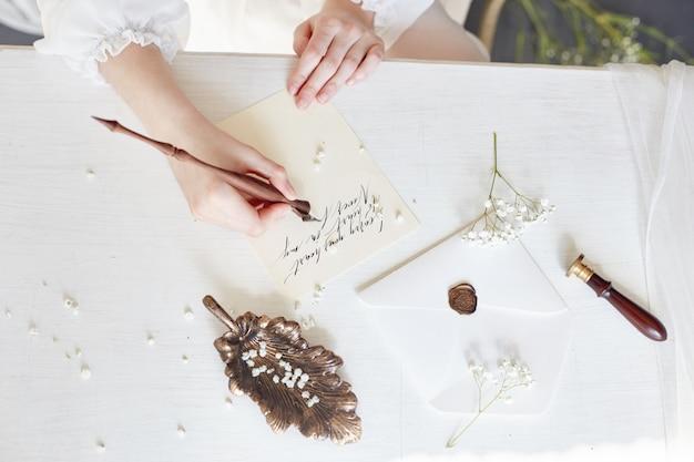 女の子は家で彼女の最愛の人に手紙を書く