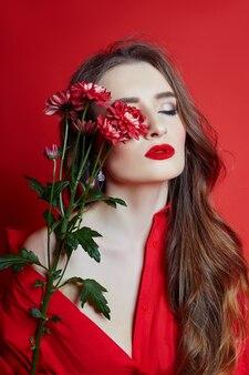 赤いドレスと花の手で巻き毛を持つ女性
