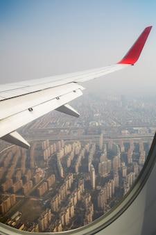 雲の上を飛んでいる飛行機の翼。人々は飛行機の窓から空を見ています