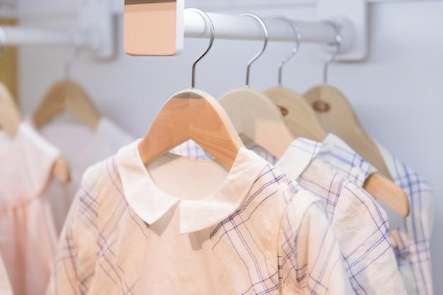 オーストラリア、メルボルンのデザイナーブランドの洋服店の棚に衣服がハングします。