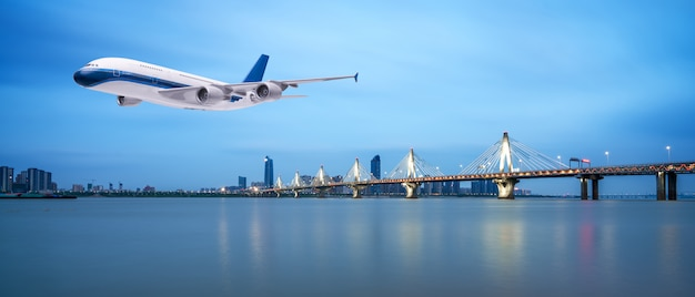 美しい夕日や日の出の風景の背景で熱帯の海の上を飛んでいる飛行機
