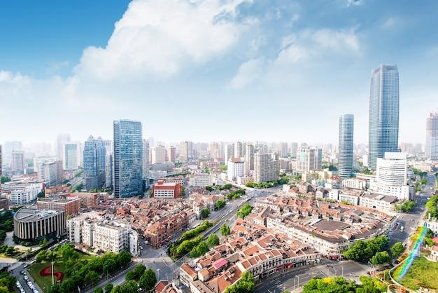 上海の高密度中央ビジネスエリアの空撮。高層ビルやガラス張りの高層ビル。複数の車線と緑豊かな都市公園がある都市道路。中国、上海