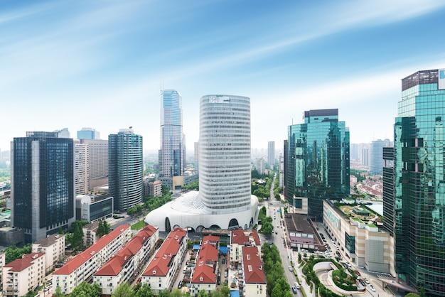 上海の高密度中央ビジネスエリアの空撮。ガラス張りの高層オフィスビルと高層ビル。複数の車線と緑豊かな都市公園のある都市道路。中国、上海