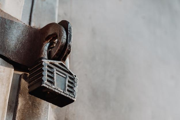 小屋の形をした南京錠は、閉じた門のヒンジに掛かっています。金属ゲート。
