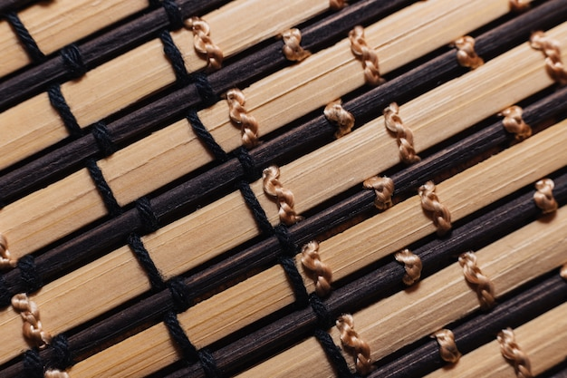 竹の棒は白とベージュの糸で結ばれています。テーブルのクローズアップのための木製の棒の敷物。